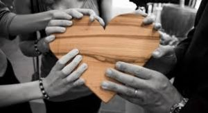 Five hands holding a wooden heart